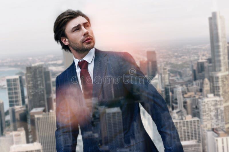 Pensando al futuro Uomo d'affari bello in vestito alla moda che distoglie lo sguardo mentre stando all'aperto con il paesaggio ur fotografia stock