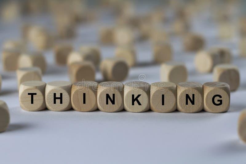 Pensando - cubo com letras, sinal com cubos de madeira imagem de stock royalty free