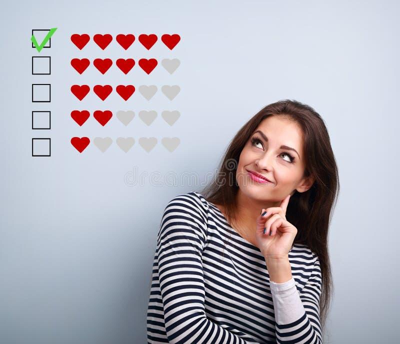 Pensando em uma jovem sorridente olhando para cima e votando em cinco corações vermelhos no ranking sobre fundo azul foto de stock