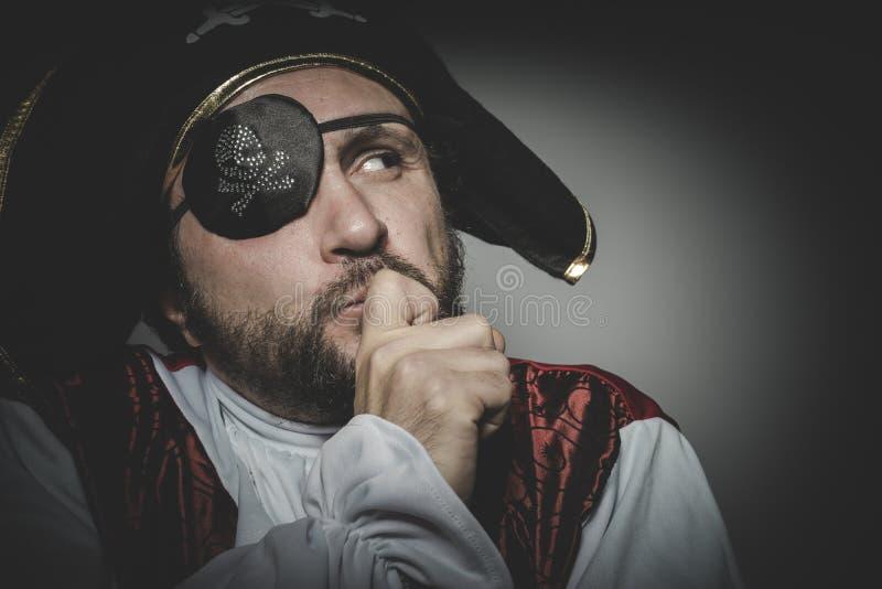 Pensando, pirata dell'uomo con la toppa dell'occhio e vecchio cappello con i fronti divertenti immagini stock libere da diritti