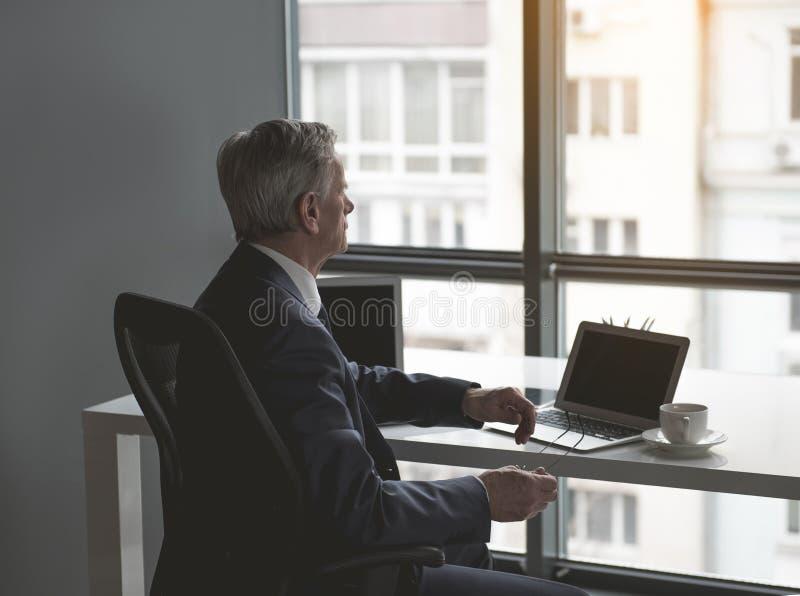 Pensativo aposente-se o homem no escritório que olha na rua fotografia de stock royalty free