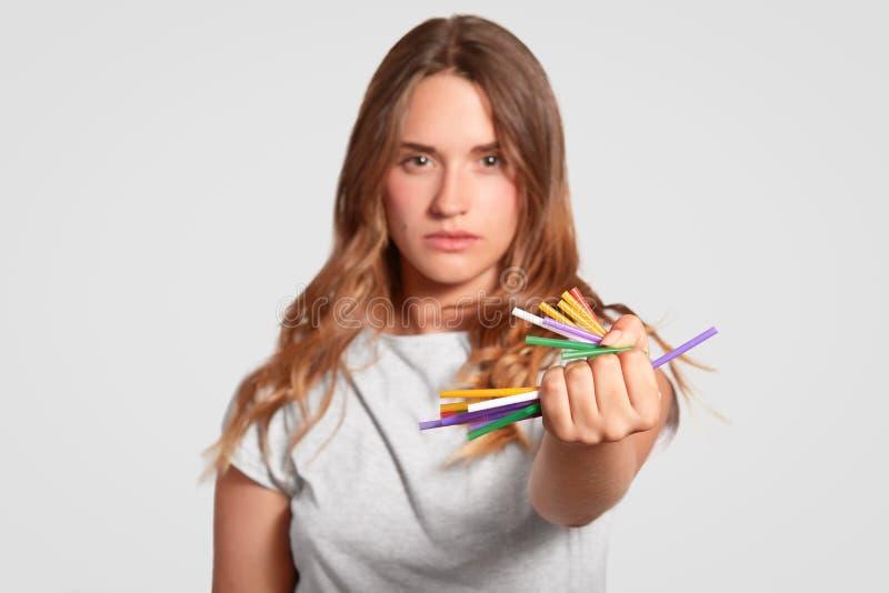Pense antes de usar palhas plásticas A mulher auto-confiante de Stong pressiona palhas coloridas bebendo à disposição, estando co fotos de stock royalty free