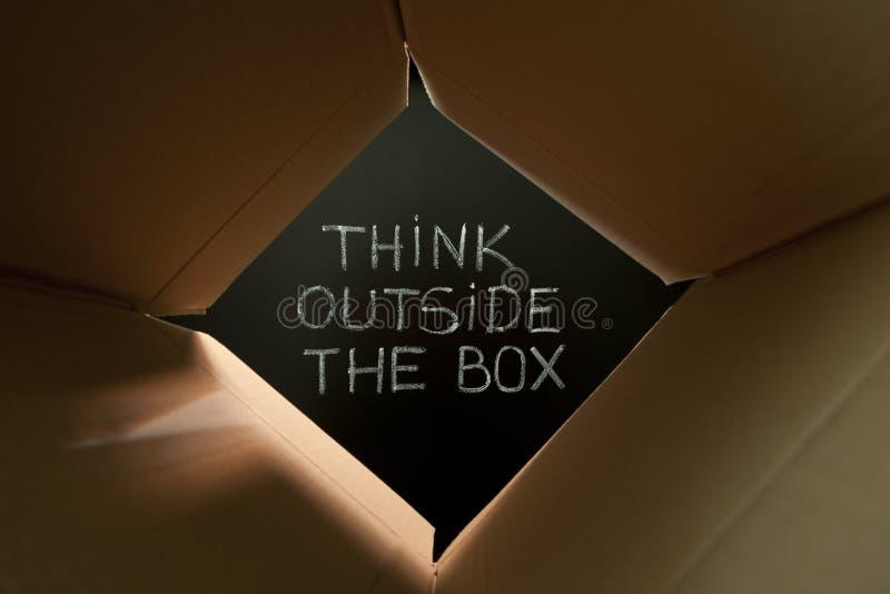 Pense fora da caixa no quadro-negro imagens de stock