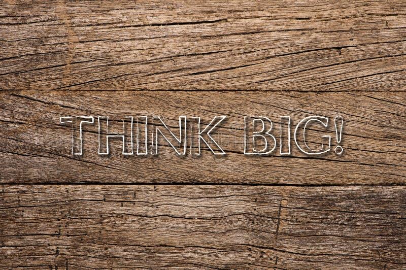 Pense grande escrito no fundo de madeira fotografia de stock
