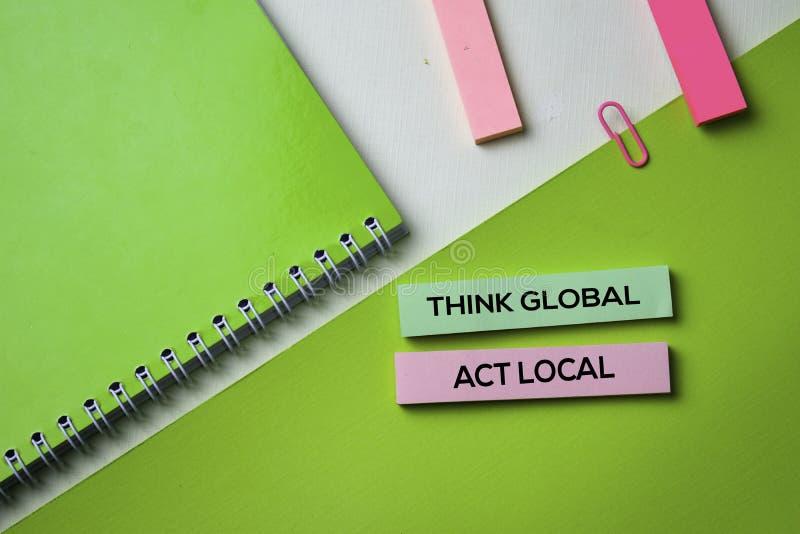 Pense o texto local do ato global na tabela da mesa de escritório da vista superior do local de trabalho do negócio e dos objetos imagens de stock