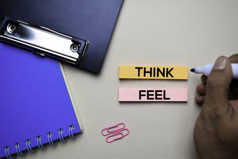 Pense ou sinta o texto em notas pegajosas com conceito da mesa de escritório imagem de stock royalty free