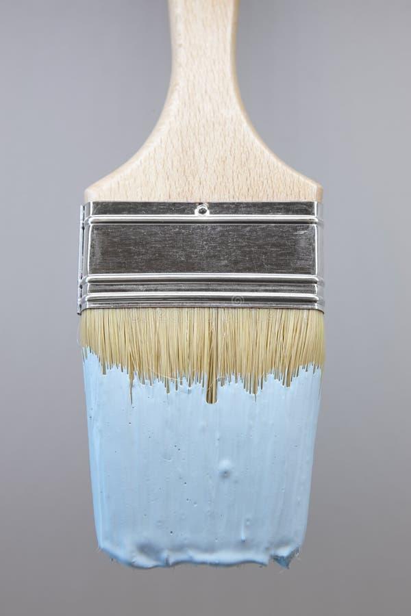 Penseel met blauwe verf en gradiënt grijze achtergrond stock afbeelding