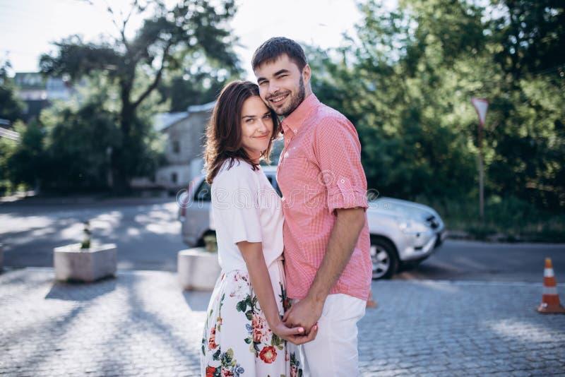 Penser au nouvel endroit à aller La belle jeune prise de sourire de couples se remet Regard à l'appareil-photo photo stock