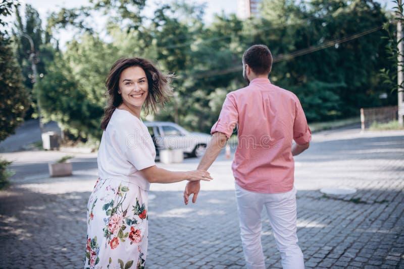 Penser au nouvel endroit à aller Les beaux jeunes couples de sourire tiennent des mains et se dépêchent à leur voiture Préparez p photos libres de droits