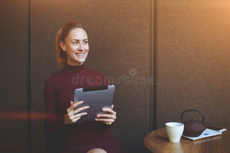 Penser femelle de sourire à quelque chose positive pendant le travail sur le comprimé numérique photos libres de droits