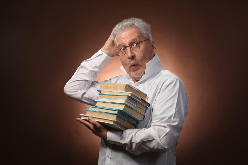 Penseur scientifique, philosophie, homme aux cheveux gris plus âgé dans une chemise blanche avec livres, avec la lumière de studi photo stock