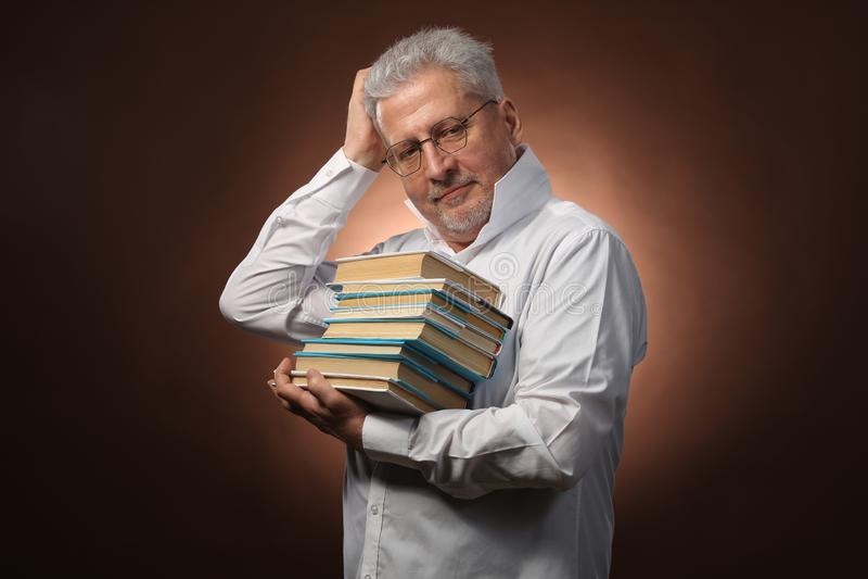 Penseur scientifique, philosophie, homme aux cheveux gris plus âgé dans une chemise blanche avec livres, avec la lumière de studi images stock