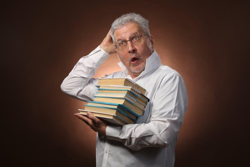 Penseur scientifique, philosophie, homme aux cheveux gris plus âgé dans une chemise blanche avec livres, avec la lumière de studi photos stock