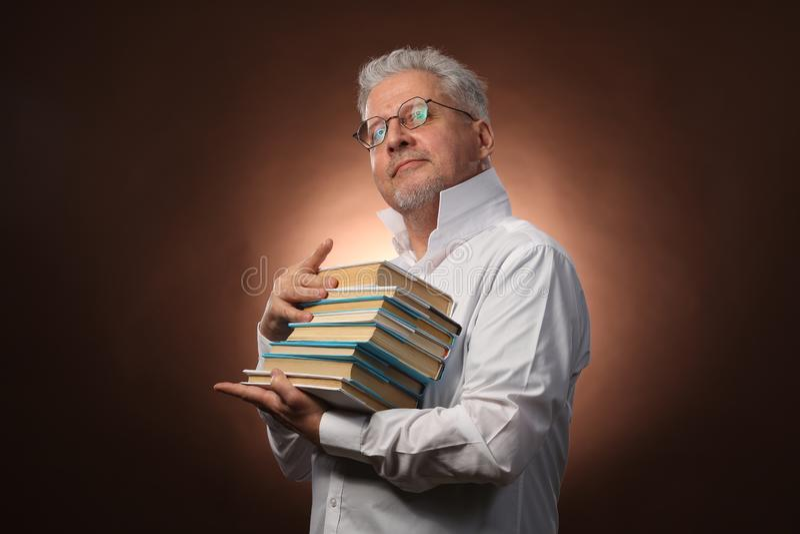Penseur scientifique, philosophie, homme aux cheveux gris plus âgé dans une chemise blanche avec livres, avec la lumière de studi photographie stock libre de droits