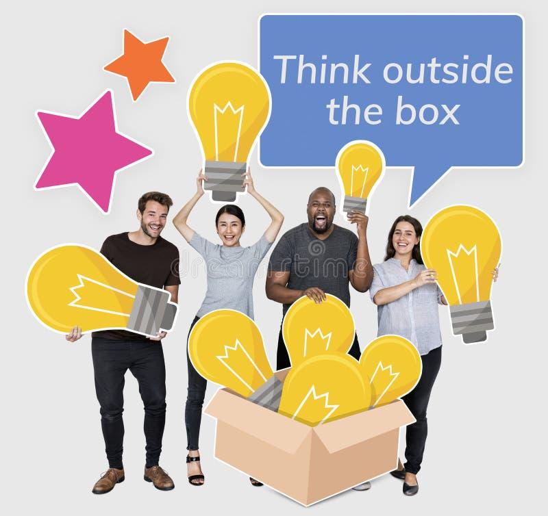 Pensez en dehors des personnes de boîte avec des symboles d'ampoule image libre de droits