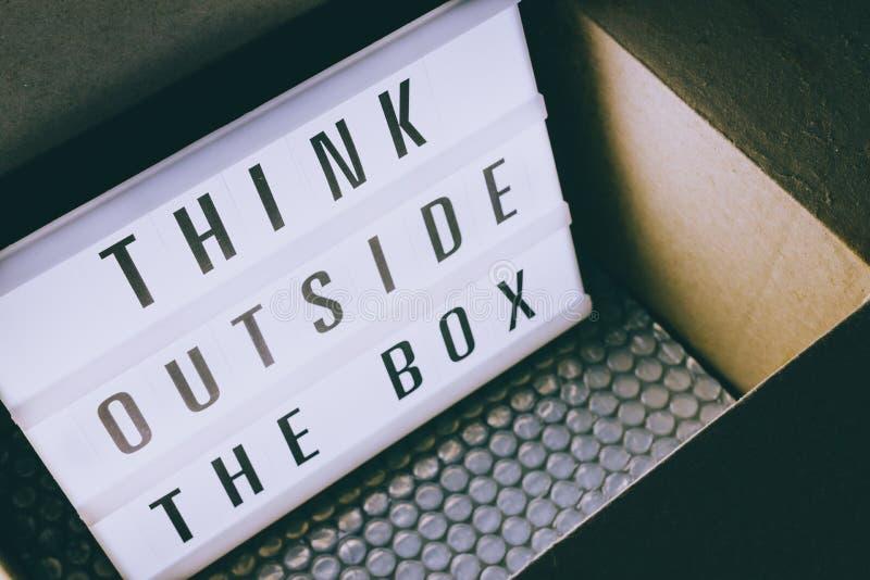 Pensez en dehors du message de boîte sur le lightbox sortant d'un colis photos libres de droits