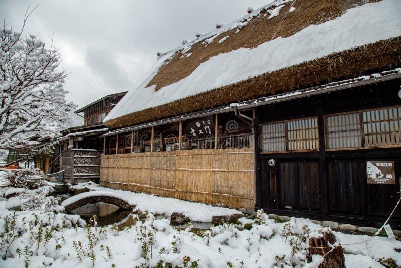 Pensión en el pueblo de Shirakawago en Gifu, Japón con la cubierta de nieve foto de archivo
