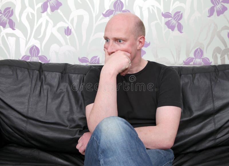 Pensiero del sofà dell'uomo scosso immagini stock