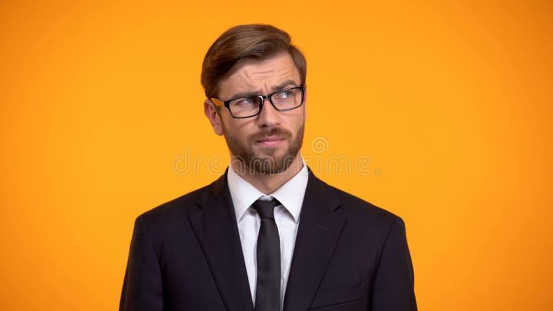 Pensiero maschio pensieroso alle idee di affari per l'inizio su, fondo arancio immagini stock libere da diritti