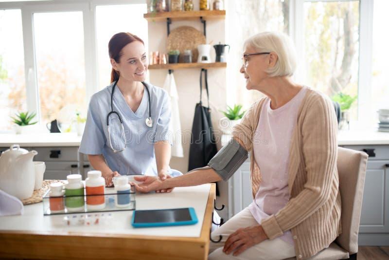Pensioengerechtigde met een bril spreken met verpleegkundige royalty-vrije stock afbeeldingen