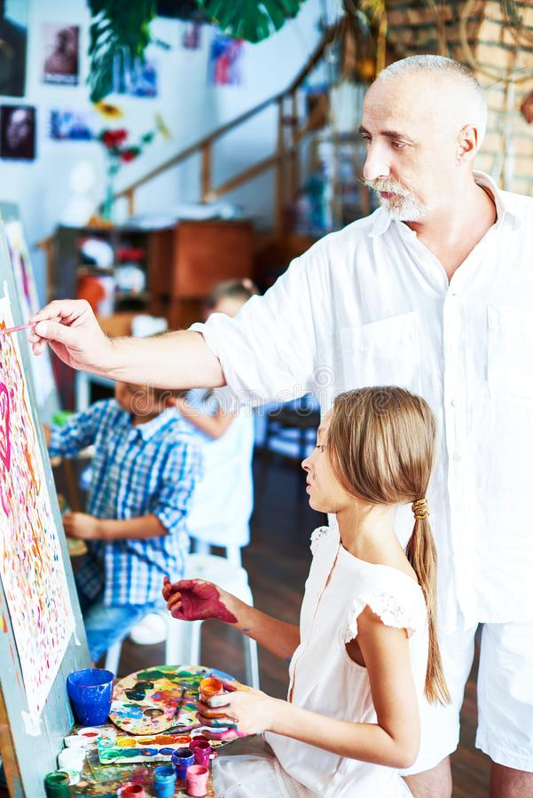 Pensionär Art Teacher Helping Girl royaltyfri foto