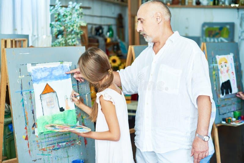 Pensionär Art Teacher Helping Little Girl i studio royaltyfri foto
