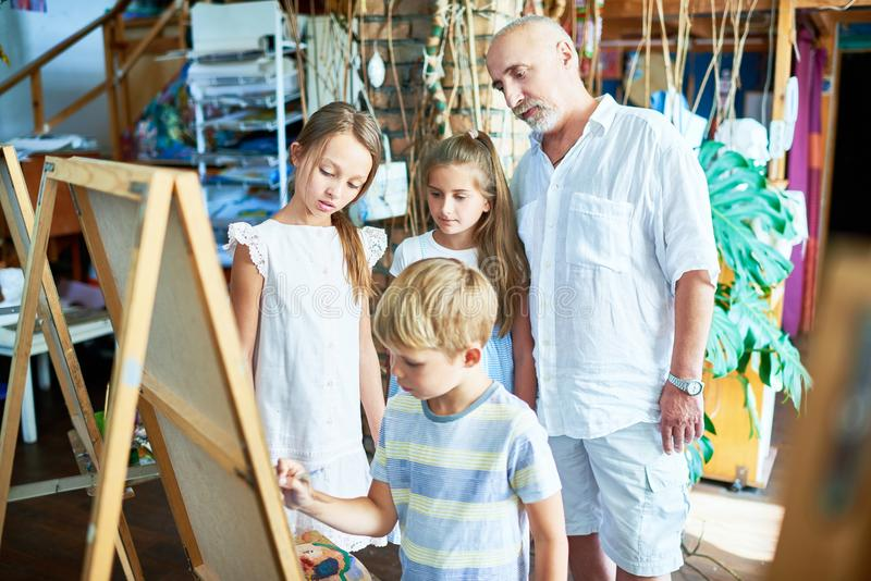 Pensionär Art Teacher med gruppen av ungar i studio fotografering för bildbyråer