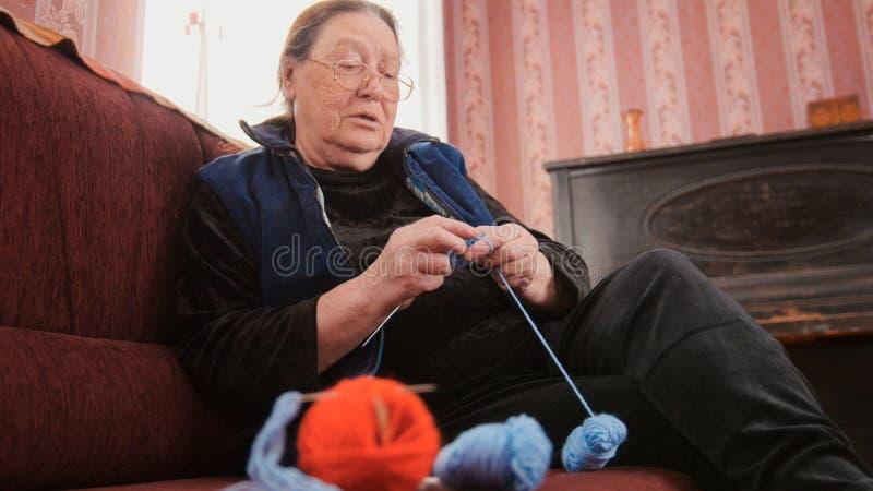 Pensionär der alten Frau trifft haus- Knitswolle das Sitzen auf dem Sofa - älteres Damenhobby hart stockfotos