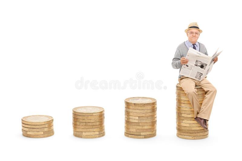 Pensionär, der die Nachrichten auf einem Stapel von Münzen liest lizenzfreies stockfoto