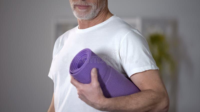 Pensionär, der Yogawolldecke, Konzept von Trainings und gesunden Lebensstil am hohen Alter hält lizenzfreie stockfotos