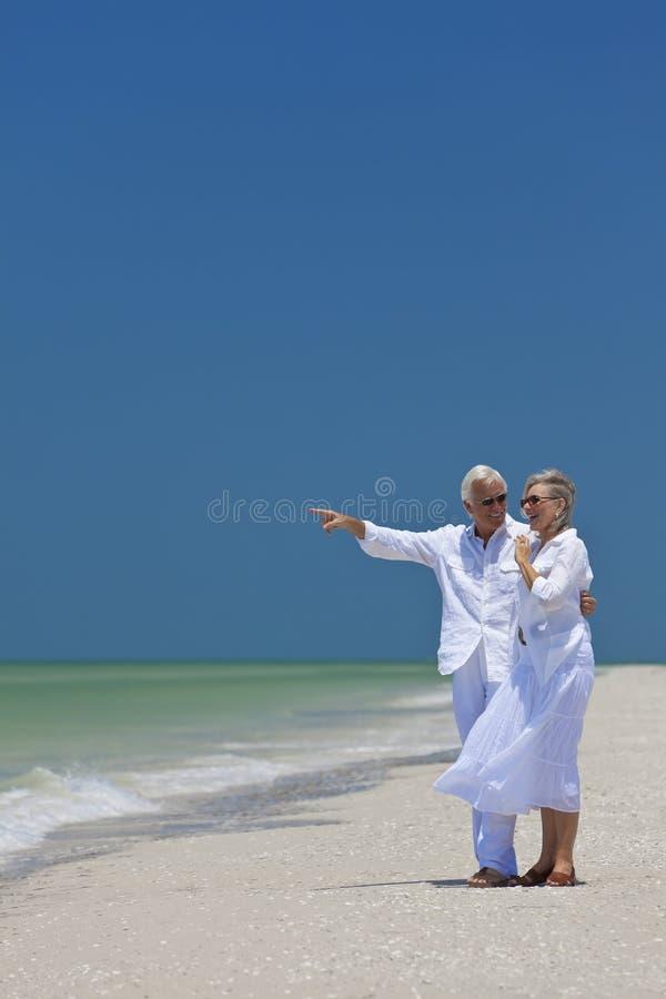 pensionär för hav för strandpar lycklig pekande till arkivfoto