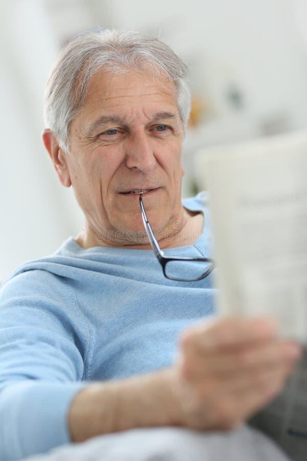 pensionär för mantidningsavläsning arkivbild