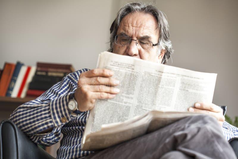 pensionär för mantidningsavläsning arkivfoto