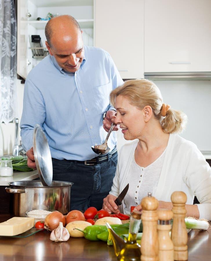 Pensionär med den mogna frun som ler och förbereder mat fotografering för bildbyråer