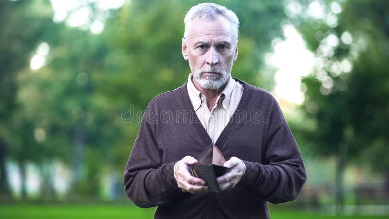 Pensionär med den tomma plånboken som ser in i kameran, armod, finanskris royaltyfria foton