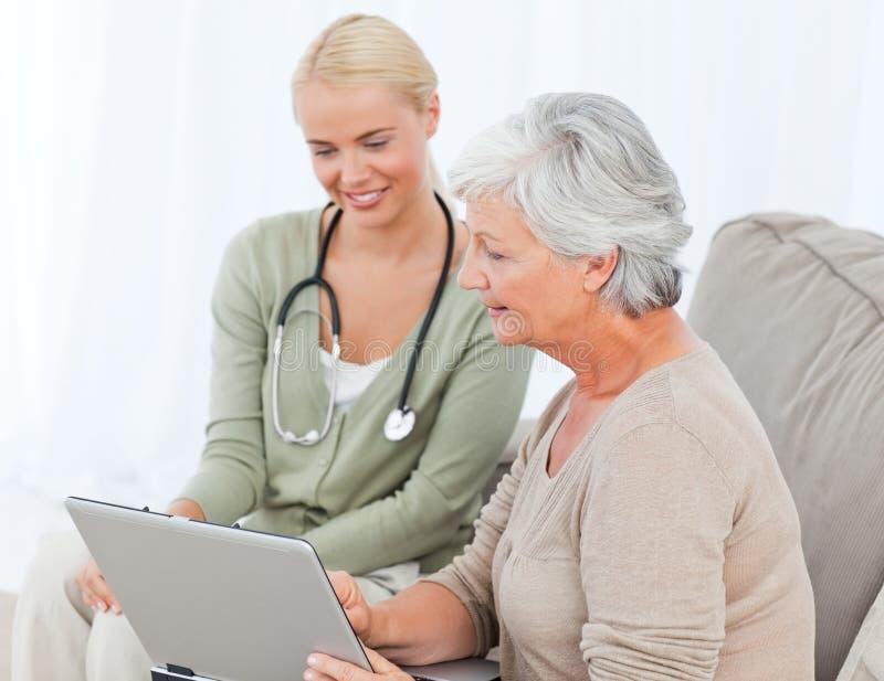 Pensionär med henne doktor som fungerar på bärbar dator 免版税库存图片
