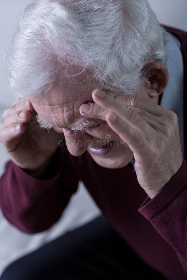 Pensionär med huvudvärk arkivbilder