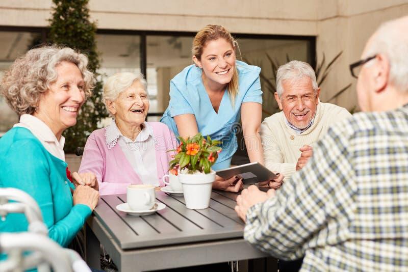 Pensionär och anhörigvårdare med minnestavladatoren arkivbilder