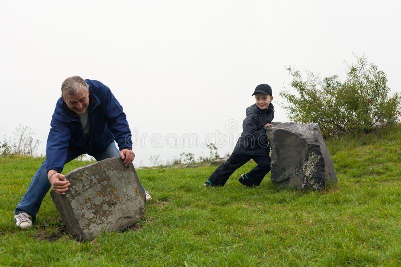 Pensionär och barn som flyttar den stora stenblocket royaltyfria bilder