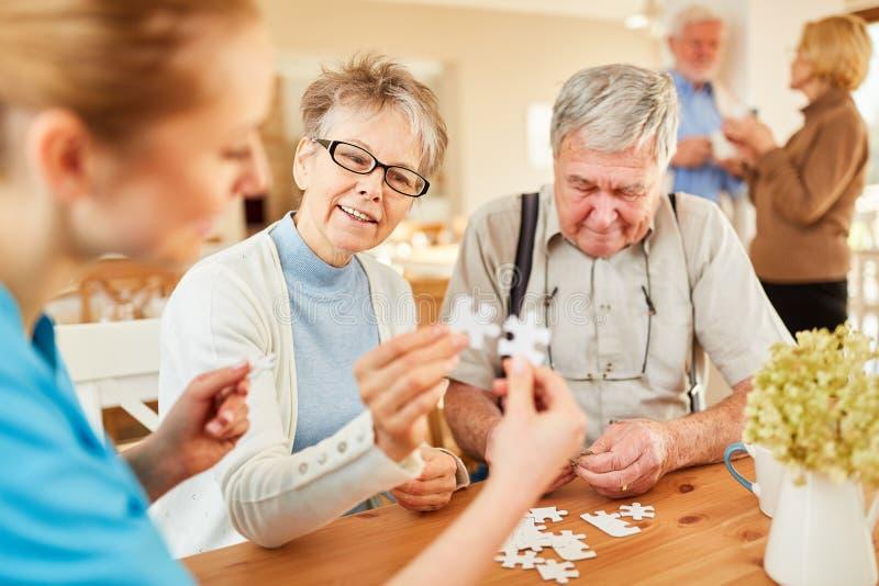 Pensionär och geriatriker som spelar pusslet arkivbild