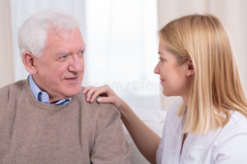 Pensionär och hög omsorgassistent royaltyfri fotografi