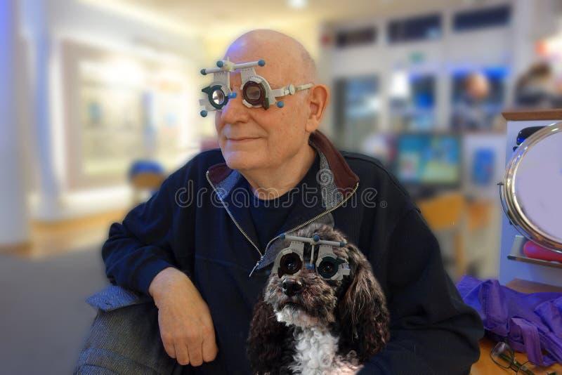 Pensionär och hans hund som testar nya linser royaltyfri foto