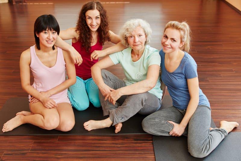 Pensionär och unga kvinnor i yogagrupp arkivfoto