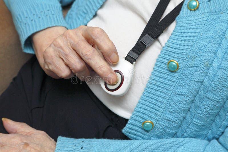 Pensionär som använder ett nödlarm royaltyfri fotografi