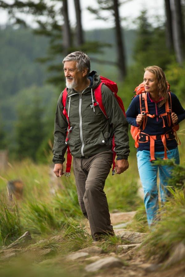 Pensionär som fotvandrar i höga berg med hans dotter fotografering för bildbyråer