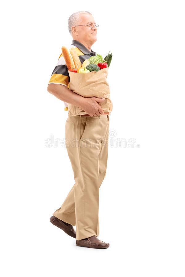 Pensionär som går med en påse som är full av livsmedel arkivbilder