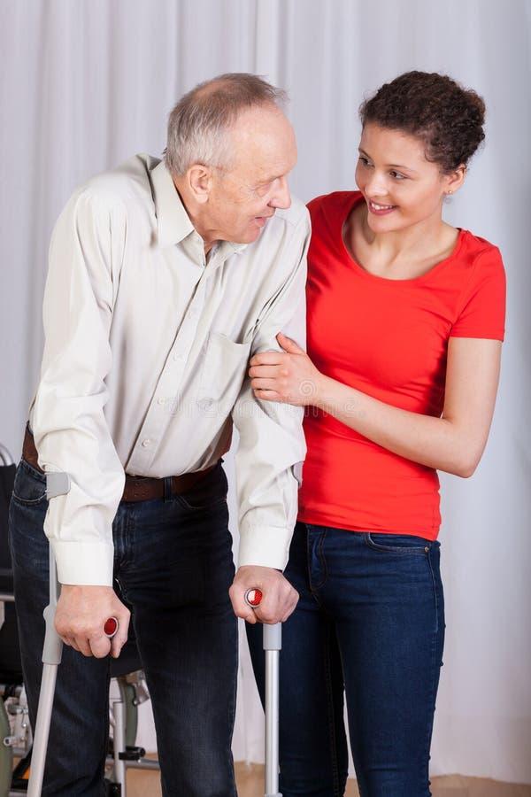 Pensionär som går med kryckor arkivfoton