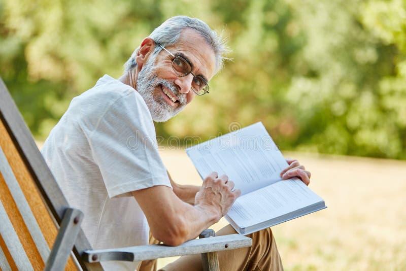 Pensionär som rymmer en bok och le royaltyfria bilder