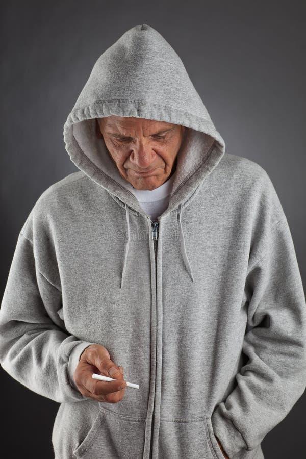 Pensionär som rymmer en cigarett fotografering för bildbyråer