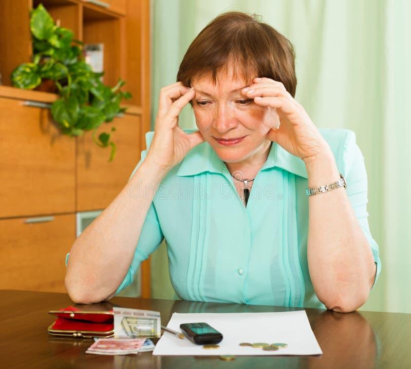 Pensionär som ser räkningar och räknar pengar royaltyfri fotografi